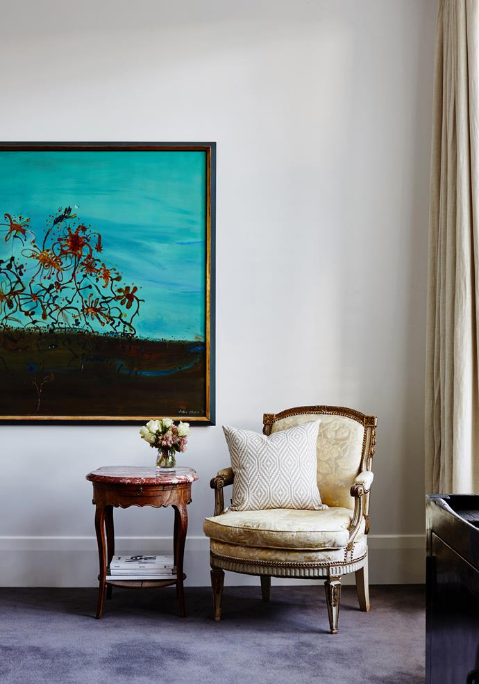 Streams of afternoon western light illuminate a colourful artwork by John Olsen in a relaxed corner of the house.