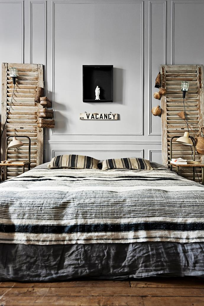 Distressed shutters frame the bed and are perfect for hanging Arianne's collection of small woven baskets and ropey reading lights.