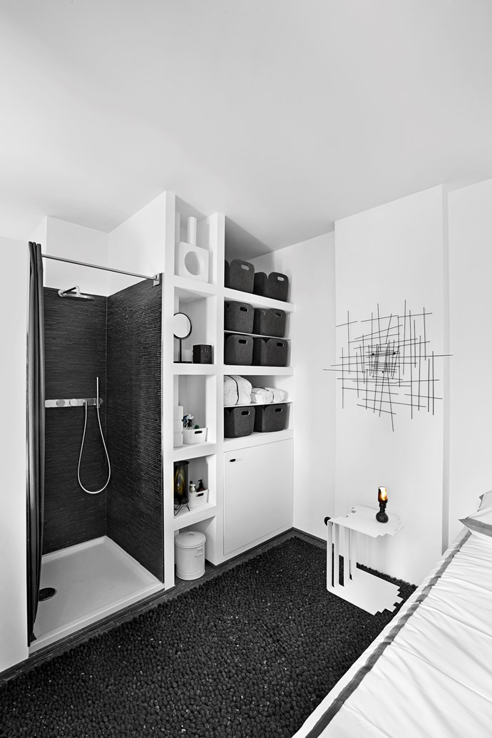 The sleeping zone is located in a cosy nook in the rear of the apartment near the shower area. Here, shelves are filled with charcoal grey baskets for extra storage.