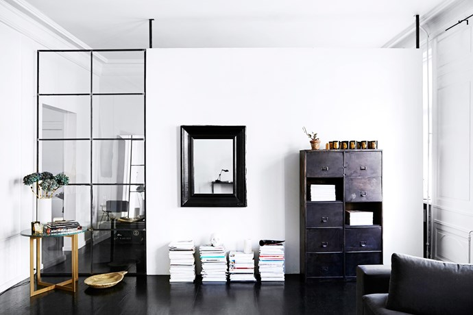 A steel-framed gridded window wall was installed to partition off the living room from the dressing room, while still allowing light to flow through. Mirrors, too, help to bounce light around the space.