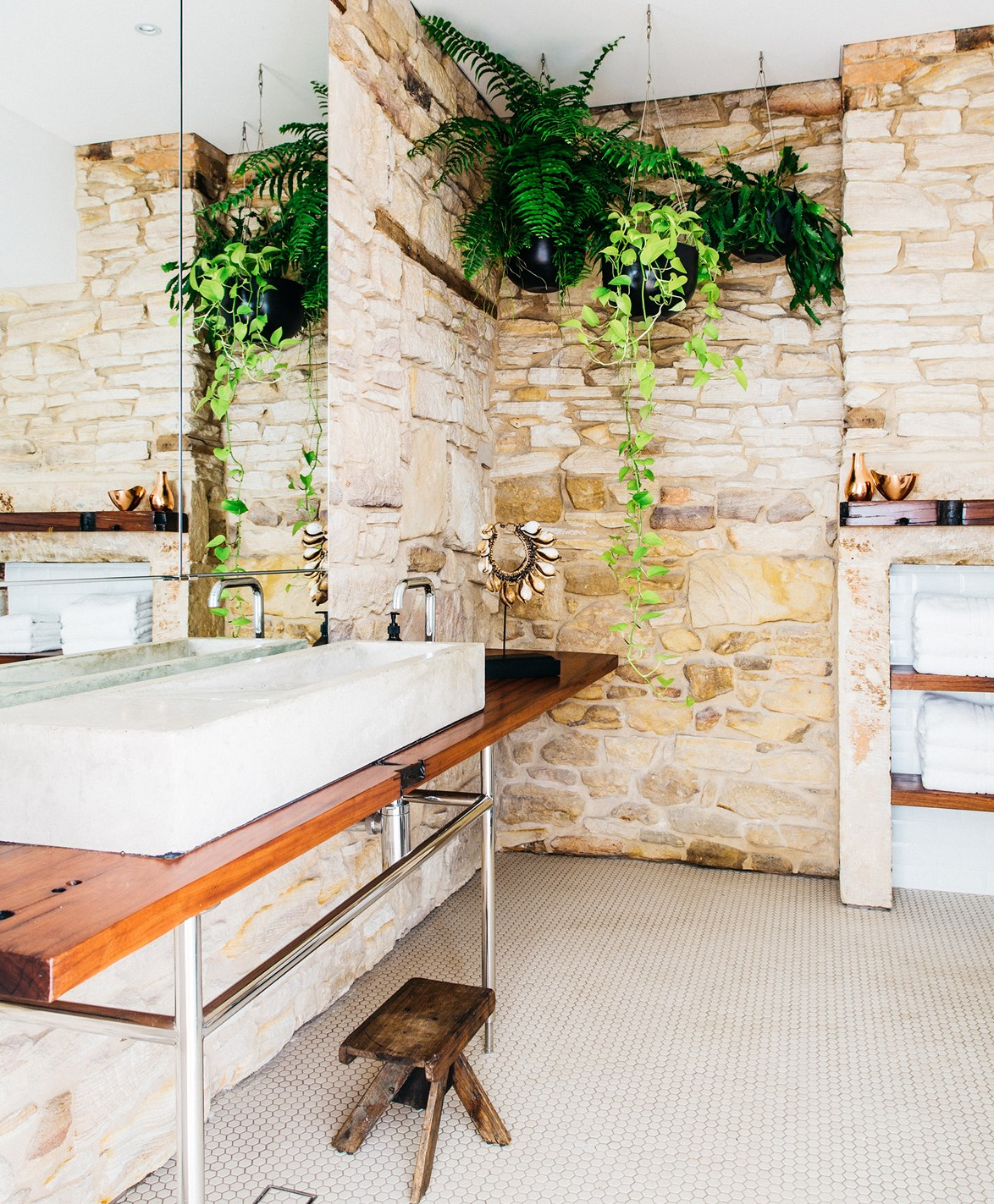 Hanging pots and greenery create a resort-like feel in this sandstone bathroom.