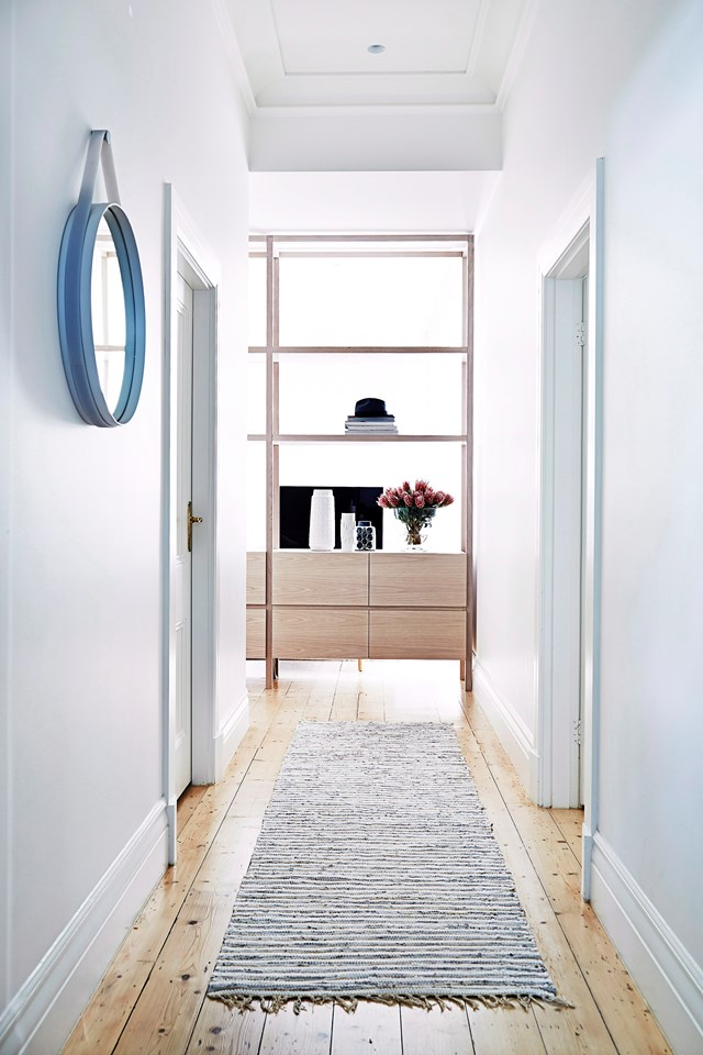 A shelving unit strategically placed at the end of this hallway separates the living room room, creating more of a defined entryway.
