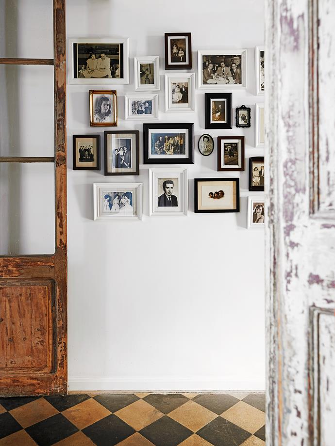 Old photos, in a selection of white, black and gold frames, are hung in a salon-style group, an artistic way to fill a large expanse of wall.