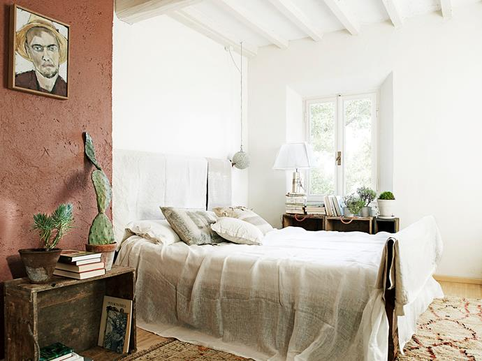 This bedroom is all about layers: rustic bedlinens, textured wall finishes and piles of books, with the addition of a prickly pear and a crassula on the crate.