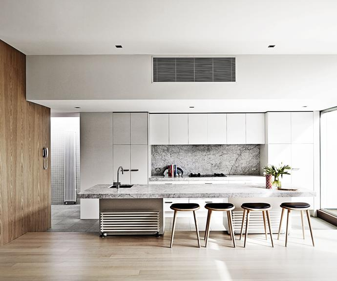 Greys, along with muted wood and marble, give this kitchen low-contrast look, while a marbled splashback adds depth.