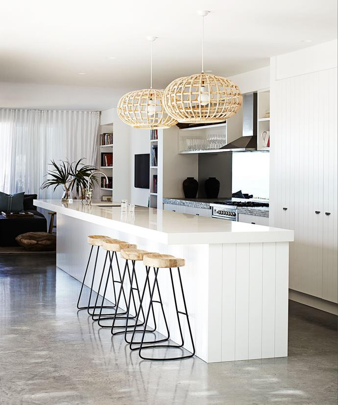 Modern, minimalist kitchens need not be harsh and unwelcoming. Here, wood features, basket-woven light fittings and greenery give a relaxed coastal feel.