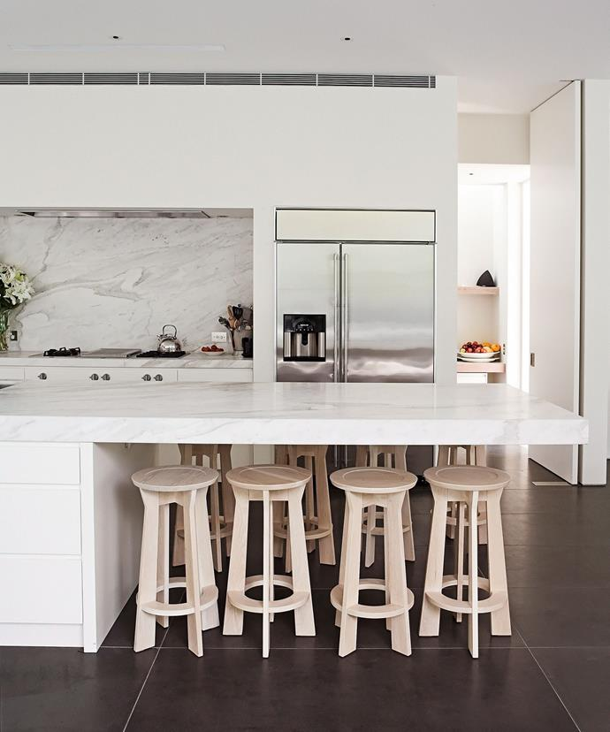 A floating marble slab doubles as a seating area under which chairs can be hidden away in this classic white kitchen.