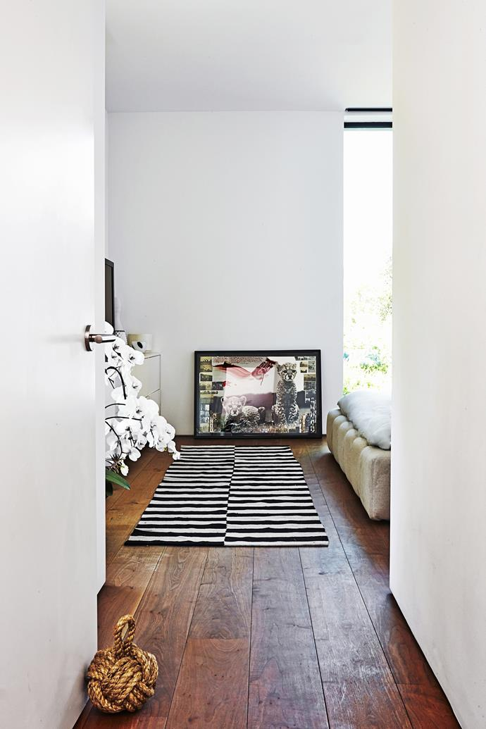 Artwork leans against the wall, leaving it relatively unadorned for a minimal, spacious feel. An antique striped Turkish rug on wide teak floorboards infuses the room with warmth and character.