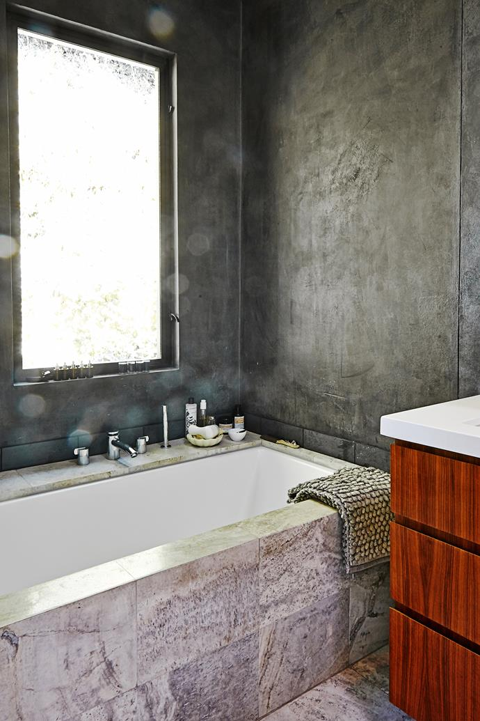 A generous ledge around the bath is perfect for bathroom accessories. Textured cement walls echo the home's exterior.
