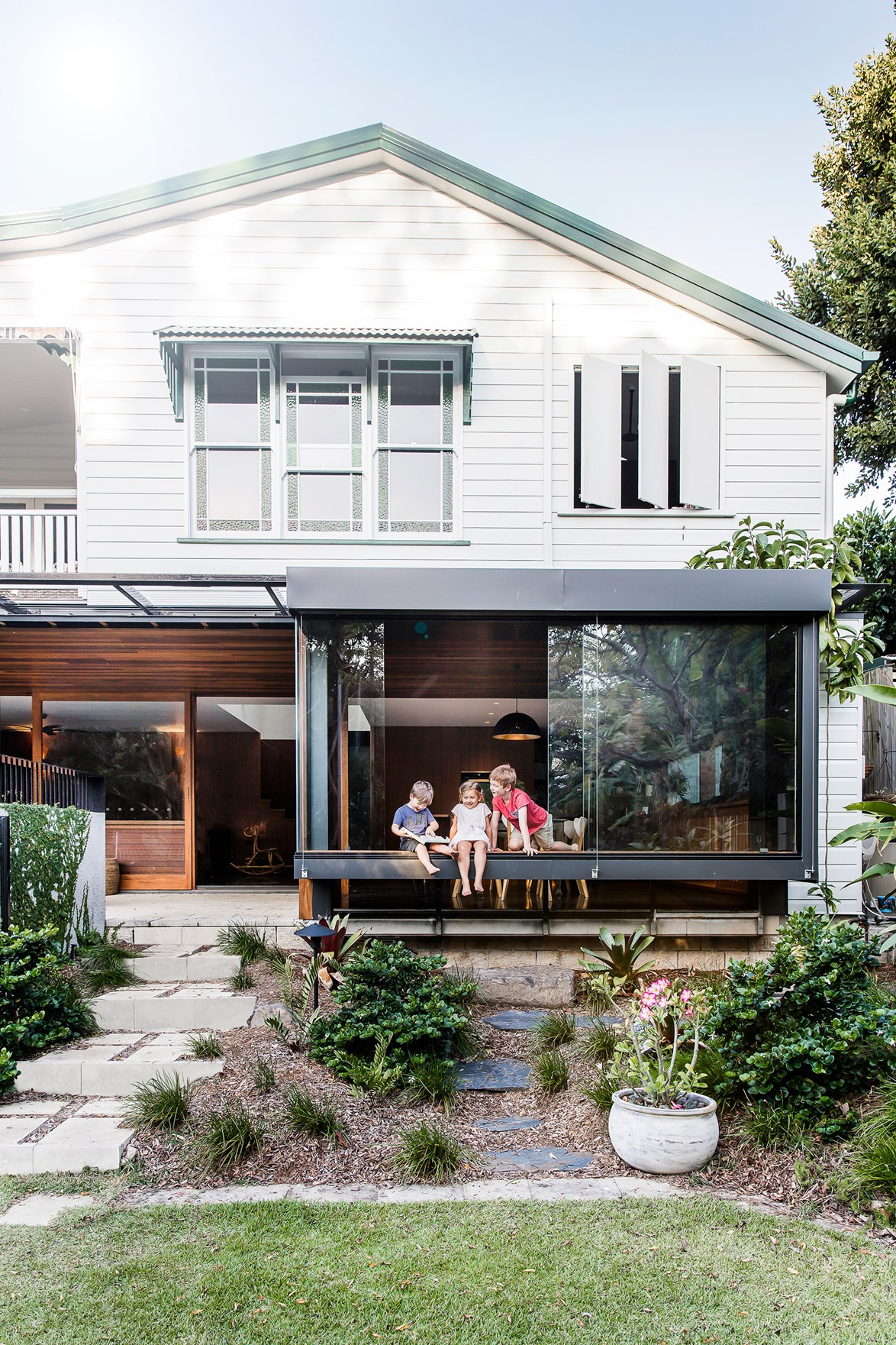 "When the owners of this [Queenslander home in Brisbane](https://www.homestolove.com.au/ground-level-queenslander-extension-4360|target=""_blank"") had their third child, they realised the existing home was no longer able to accommodate the family comfortably. They decided to overhaul the layout of the home, and added a modern extension to the first floor, containing a kitchen, dining and living room.  *Photo: Maree Homer*"