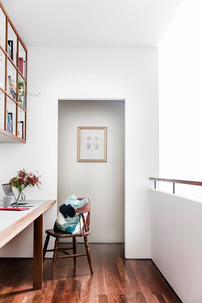 A wide passage adjacent to the stairwell contains a custom-made desk and wall-mounted shelves. A second-hand chair adds historical depth.