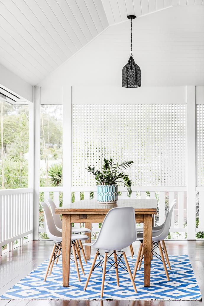 The old kitchen table has been shifted outdoors and teamed with replica Eames chairs.