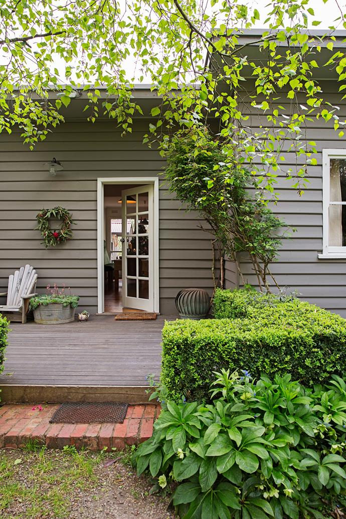 The weatherboard home is painted in a deep taupe hue that complements the lush surrounding garden.