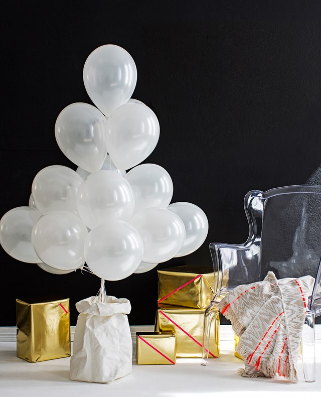 "**Balloon Christmas tree:** It's hard not to feel like a kid at Christmas and with this balloon tree it will be even more of a challenge. Arrange balloons into a ""tree"" shape, secure strings to dowel rod with sticky tape then stick the rod into the sand. Child's play!"