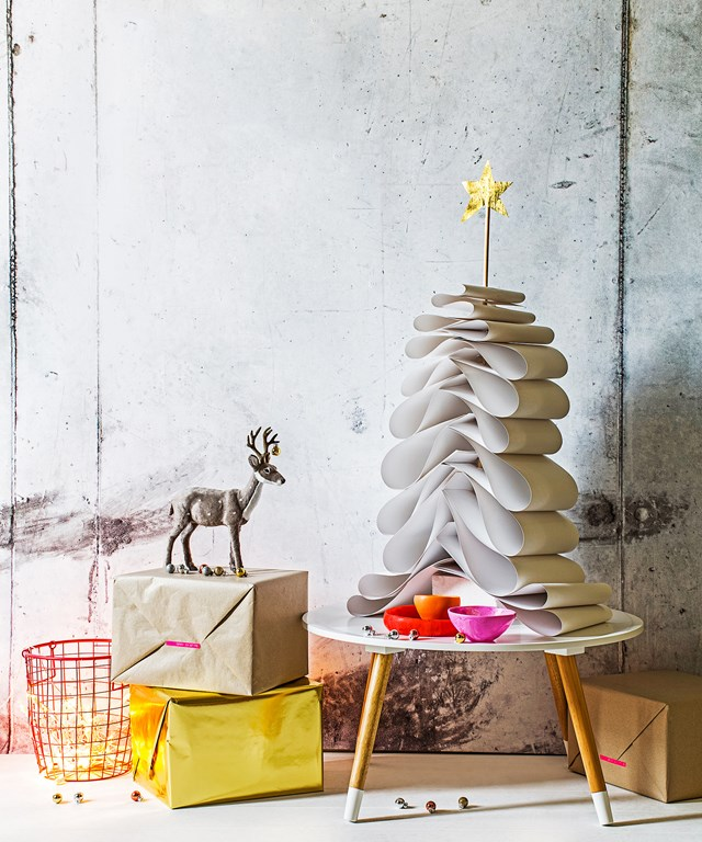 **Paper Christmas tree:** All you need to recreate this table-top tree is some white cardboard, a polystyrene foam block and a piece of dowel. Simply insert dowel into foam block, then cut cardboard into different lengths. Fold the largest piece of cardboard so ends meet, make a hole with scissors towards the edge, then thread onto dowel rod. Repeat with remaining pieces of cardboard, largest to smallest and top with a sparkly star.