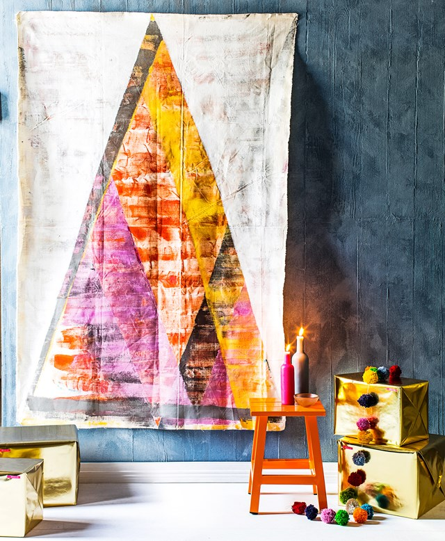 **Painted canvas Christmas tree:** An art-piece Christmas tree like this one is a clever solution for compact spaces – it can easily be folded away into a drawer when the silly season is over. All you need to make it is a sheet of canvas (in a size appropriate for your space), a thick paintbrush and a selection of paints to complement your interior. Mark out your design with masking tape, then paint away. To hang, a few tacks will do the trick.