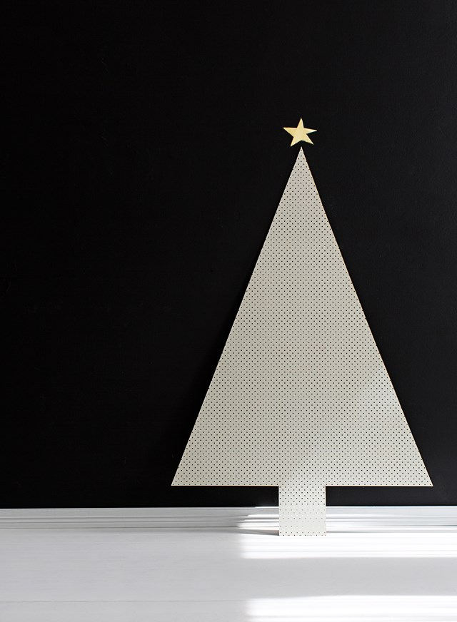 "**Pegboard Christmas tree:** If a modern-minimal look is your style, go for a tree scheme in black and white. To make this minimalistic tree, lay a piece of masonite pegboard on the ground and use a pencil and tape measure to mark out a ""tree"" shape. Use a jigsaw or Dremel saw to cut along the marked lines. Lean the tree against a plain backdrop (you can paint your tree black if you have white walls) to create an ultra-cool and contrasting Christmas scene."