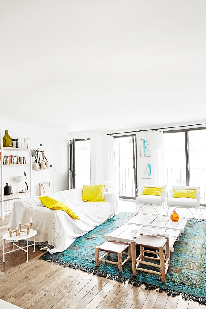 Curtains are made from linen sheets, which cover the sofa too, for a relaxed and casual feel. Yellow cushions add  a pop of sunshine to the mostly white and timber palette. The rug imitates the nearby ocean hues.