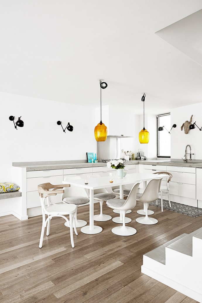 While cupboards are from Ikea in the open-plan kitchen, concrete was poured for the benchtop. Jielde wall lamps continue from the living area around the kitchen. The custom-made table's feet match the Tulip chairs.