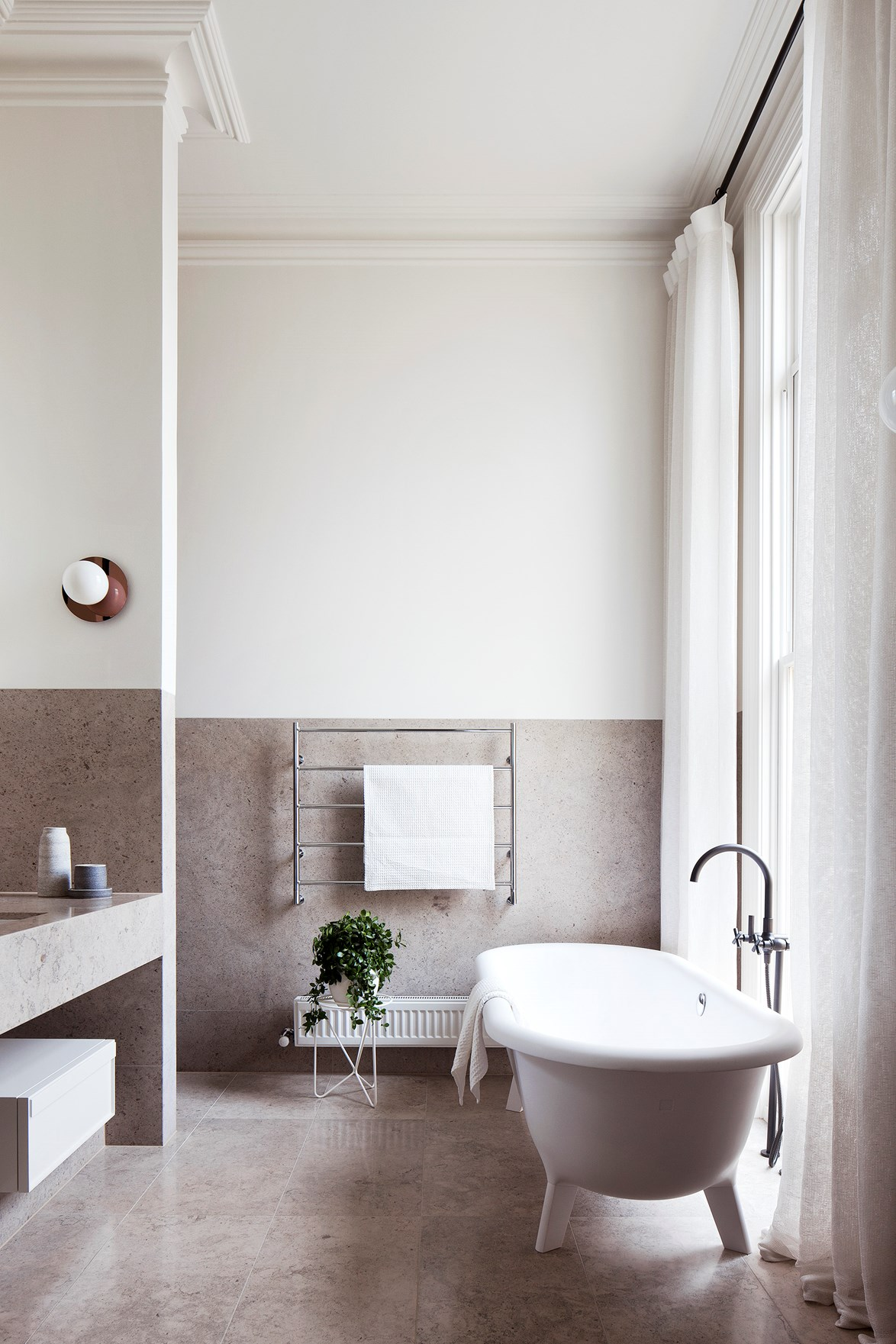 "A minimalist bathroom will never have everyday knick-knacks on display. Just like the bathroom in this [renovated Victorian terrace](https://www.homestolove.com.au/south-yarra-terrace-by-hecker-guthrie-4380|target=""_blank"") in Melbourne, which instead features stylish pottery ornaments, a modern free-standing tub and an [indoor plant](https://www.homestolove.com.au/popular-indoor-plants-2018-6496
