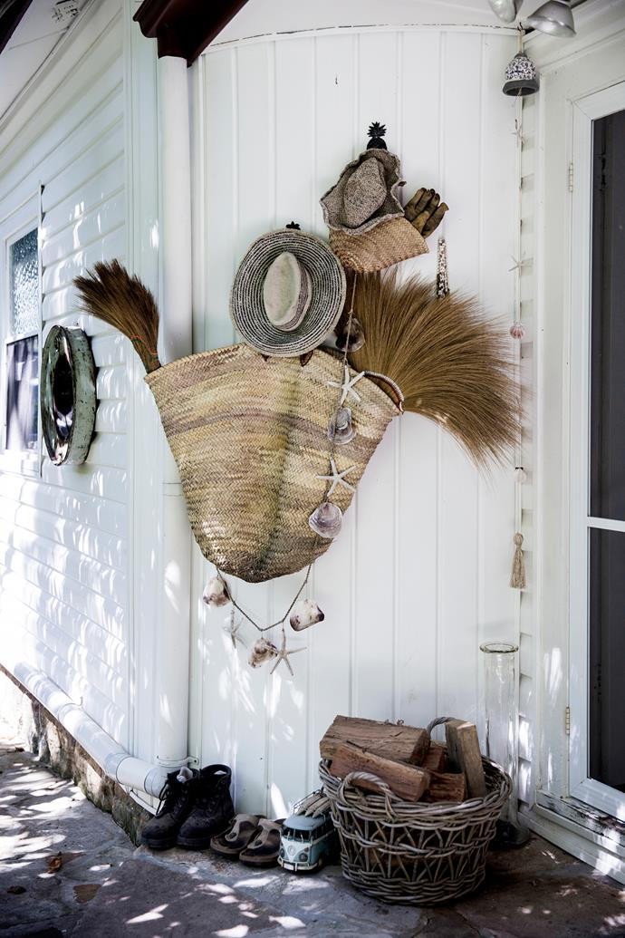 A coastal vignette of straw hats, bags and seashells hangs at the front door, creating a warm welcome.