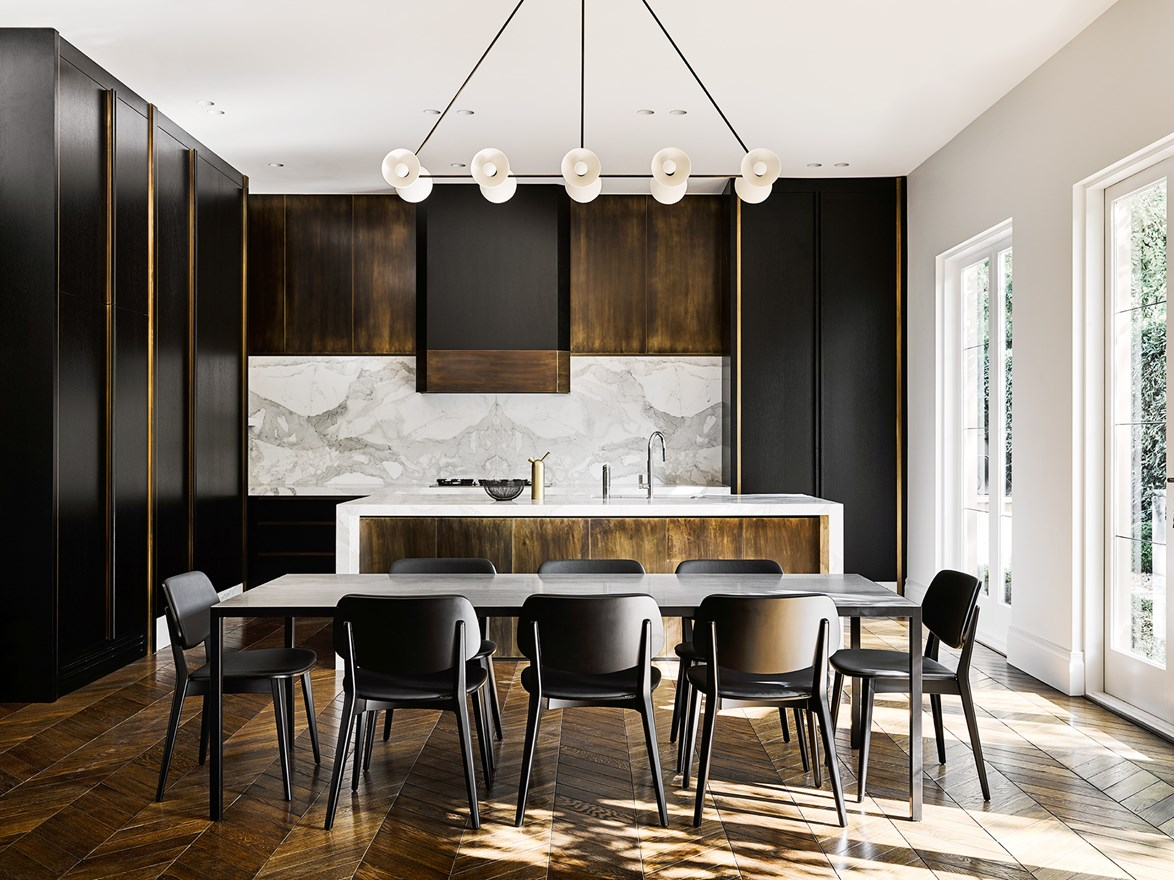 "Overhead cabinetry in folded bronze frames the Calacatta marble splashback. Herringbone parquetry has been used throughout the kitchen and dining area of this [restored georgian duplex](https://www.homestolove.com.au/luxury-renovation-of-a-georgian-style-duplex-4418|target=""_blank""), giving the home a modern French provincial feel. *Story: Belle*"