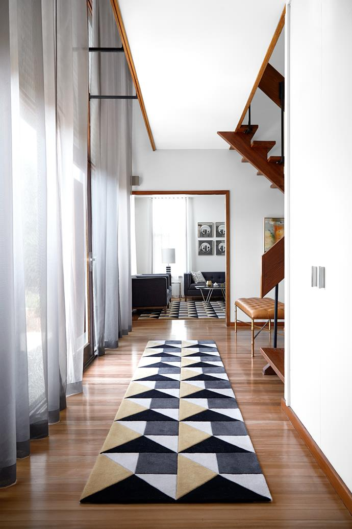 """The 'Brady Bunch' staircase leads from the entry hall to the floating gangway. The stairs, skirting boards and doors are all western red cedar and the hallway runner is from Greg Natale's New Modern collection from [Designer Rugs](http://designerrugs.com.au/ target=""""_blank"""" rel=""""nofollow"""")."""