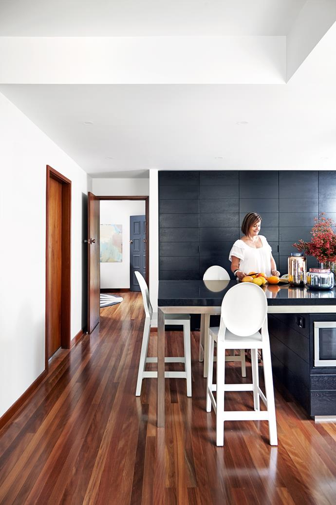 The new kitchen is connected to all the living spaces. Stewart didn't want to add more timber tones, so the joinery is ebonised American oak paired with a stainless-steel benchtop.