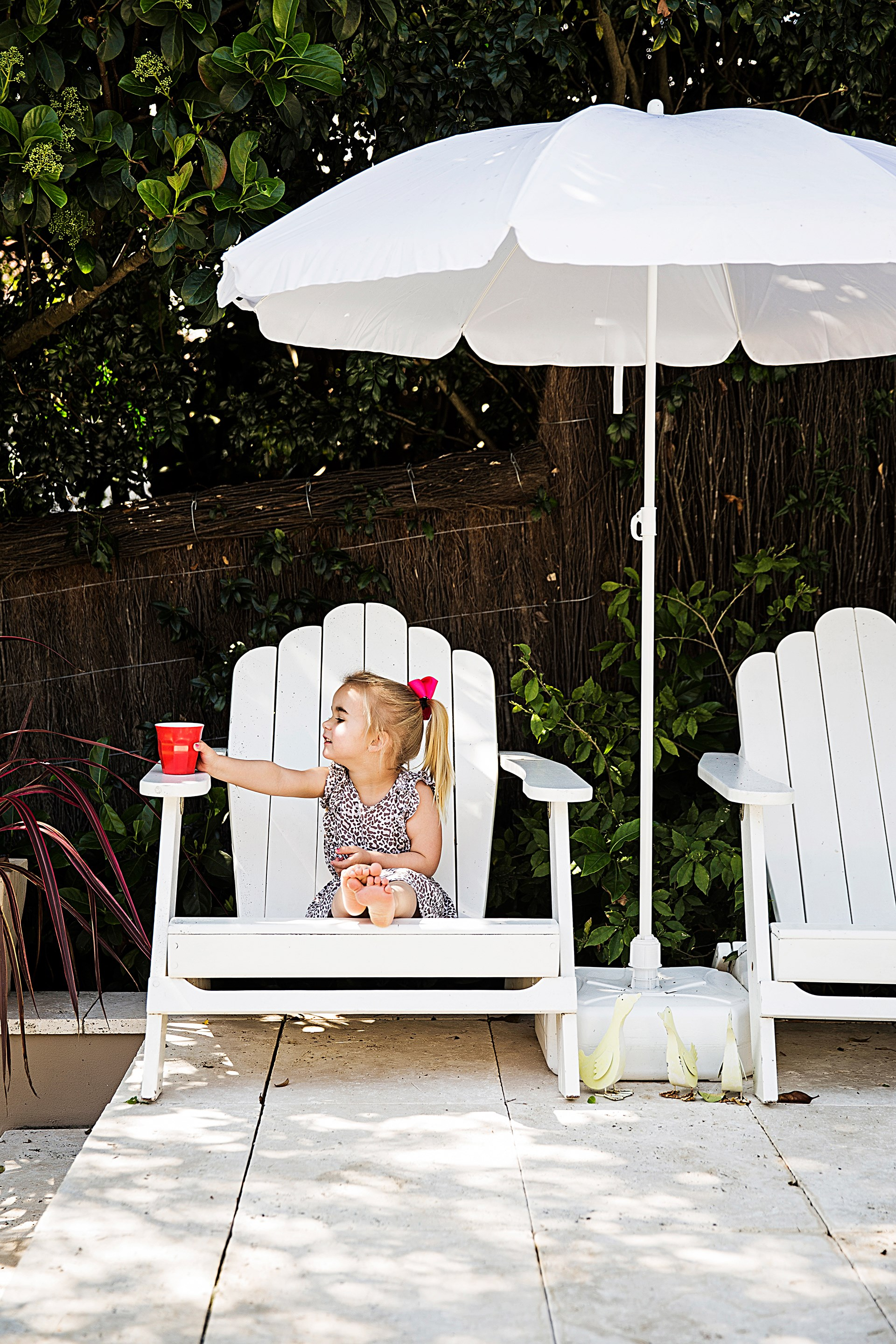 """Two adirondack chairs positioned under an umbrella are the perfect spot for a chin-wag in this [family home](http://www.homestolove.com.au/a-family-home-with-hotel-inspired-style-4440