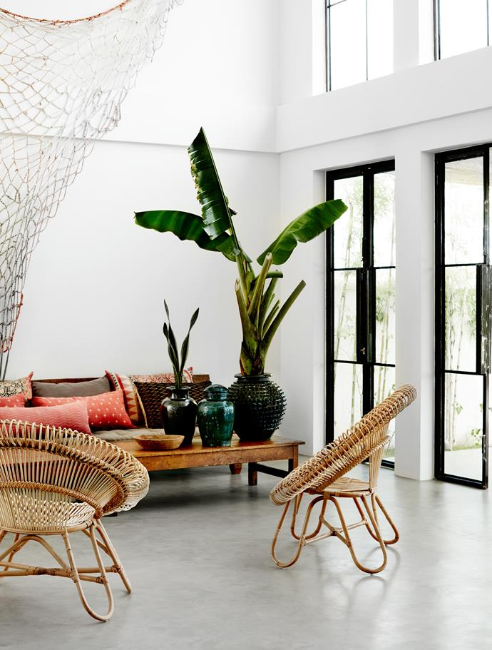 The living room has a loft-like feel with seven-metre-high ceilings. Cushions from Rabens Saloner on the sofa add colour and pattern. The handmade netting on the wall was custom dyed. Bamboo chairs and pots from Rabens Saloner.