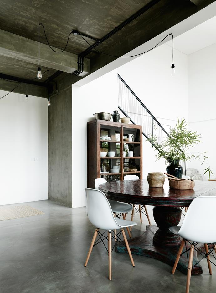 The dining area and kitchen have cement flooring which is tinted green. An unusual staircase handrail makes a bold statement in the adjacent white living room. Table, chairs and cupboard from Rabens Saloner.