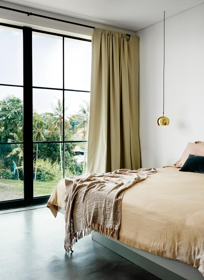 The master bedroom looks over the rice paddies framed by iron windows.Opened up, these doors blur the lines between indoors and out.