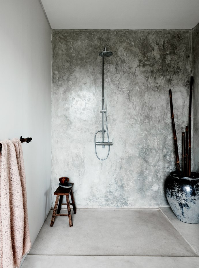 A Balinese-style cement bathroom is softened with bamboo towel rails and ornamental displays.