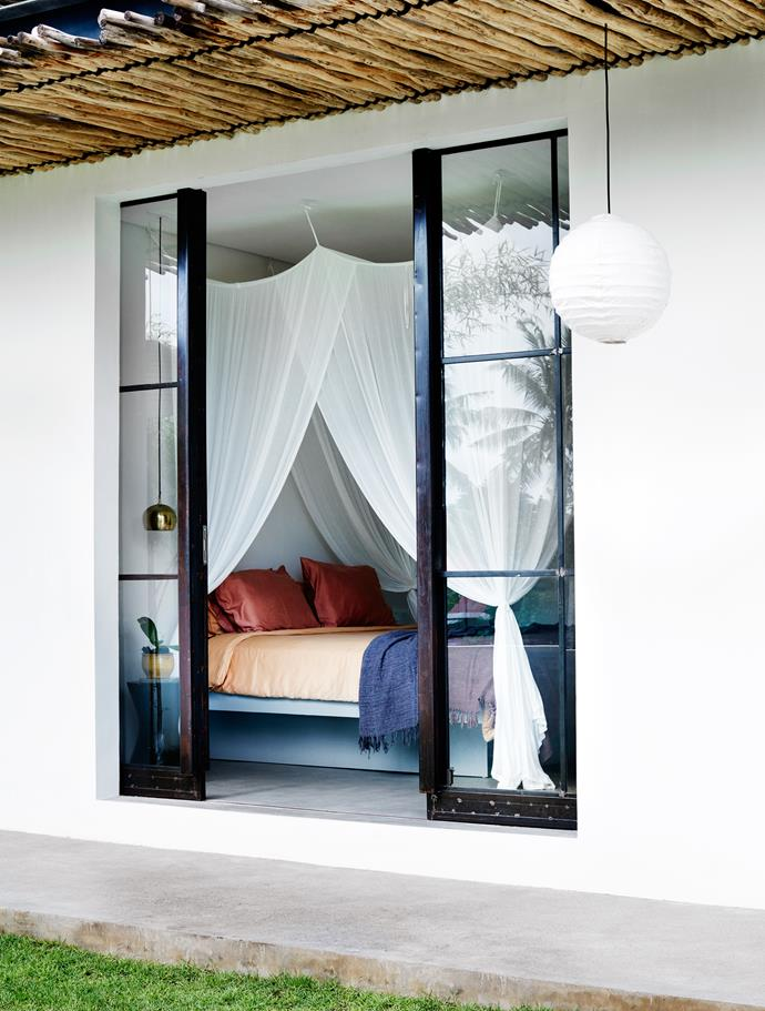 Mosquito netting adds a tropical vibe to the downstairs guest bedroom adjacent to the garden.