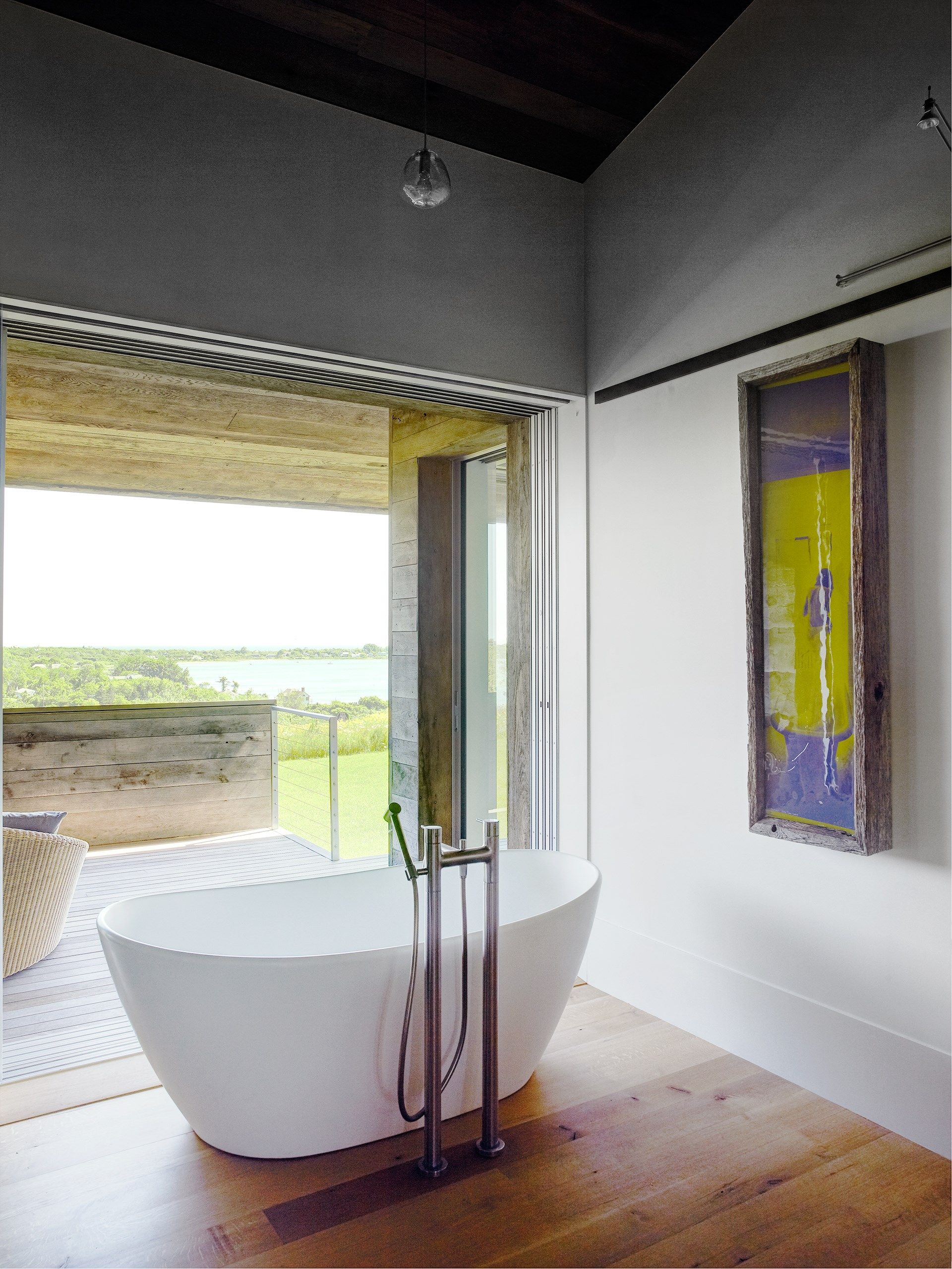 "This luxurious bathroom in a [Montauk holiday home](https://www.homestolove.com.au/luxury-montauk-house-by-bates-masi-architects-4473|target=""_blank"") opens out onto its own private deck. Hills and the waters of Lake Montauk are visible in the distance. *Photo: Richard Powers / Story: Belle*"