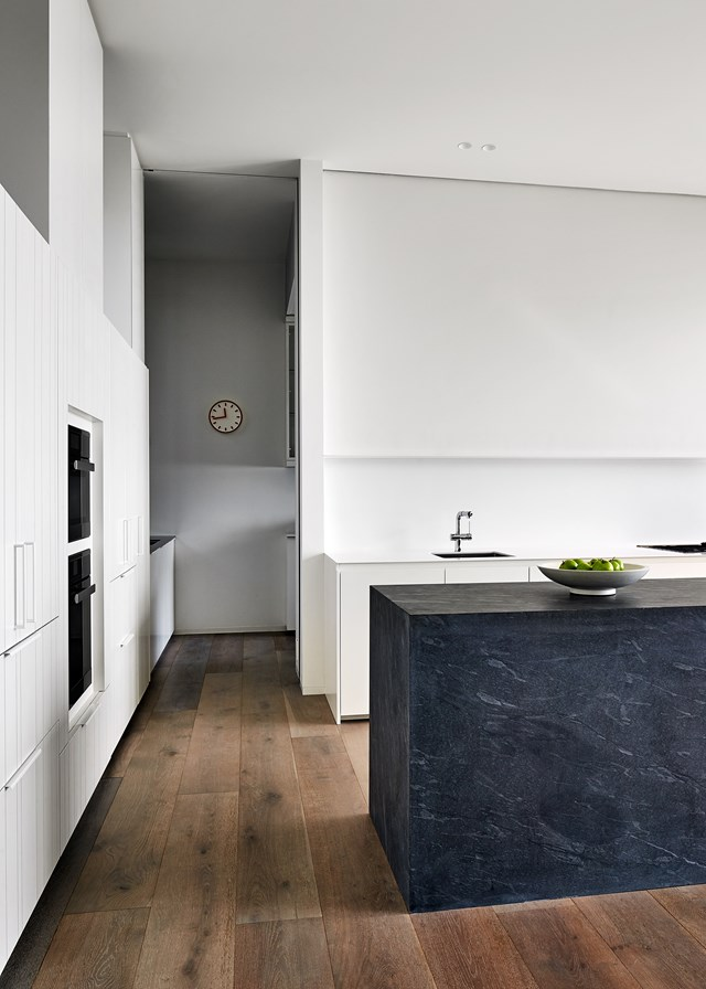 "This kitchen in a newly built [home on the Mornington Peninsula](https://www.homestolove.com.au/a-home-built-into-its-natural-surroundings-4505|target=""_blank"") is all about clean lines and textural interest. The hero of the room is the black island bench in Pietra Del Cardosa marble. *Photo: Peter Bennetts / Story: Belle*"