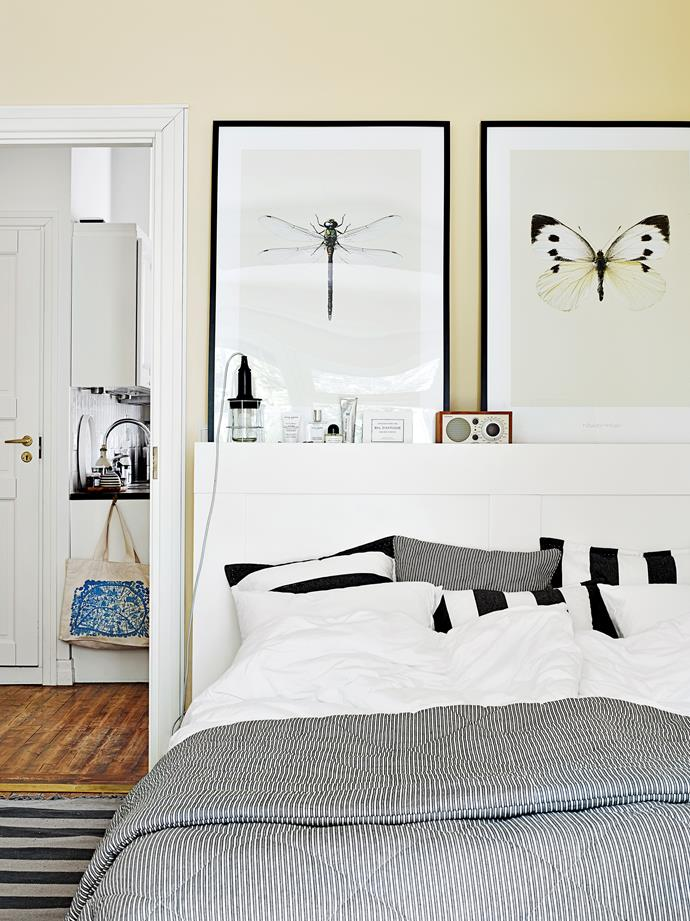 The main bedroom is painted in beige offering a softer atmosphere compared to the crisp white walls of the open-plan living area. Oversized insect prints bring a touch of nature inside.