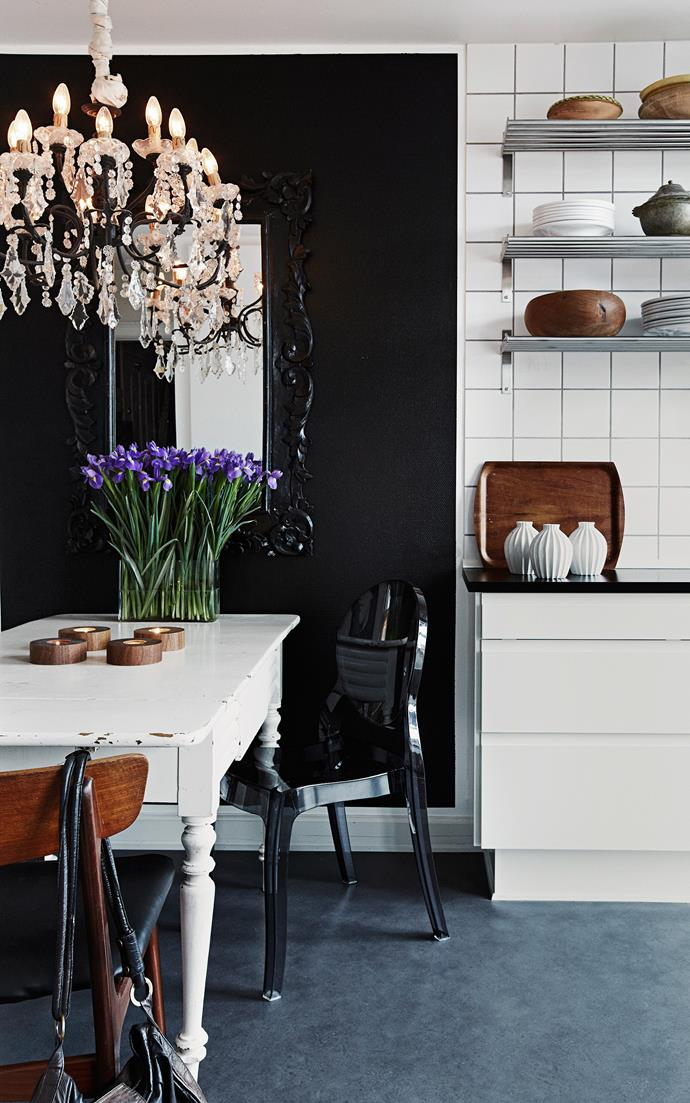 A bunch of irises, crystal chandelier and black wall create a luxe look in the dining area. Timber accessories add a down-to-earth touch.