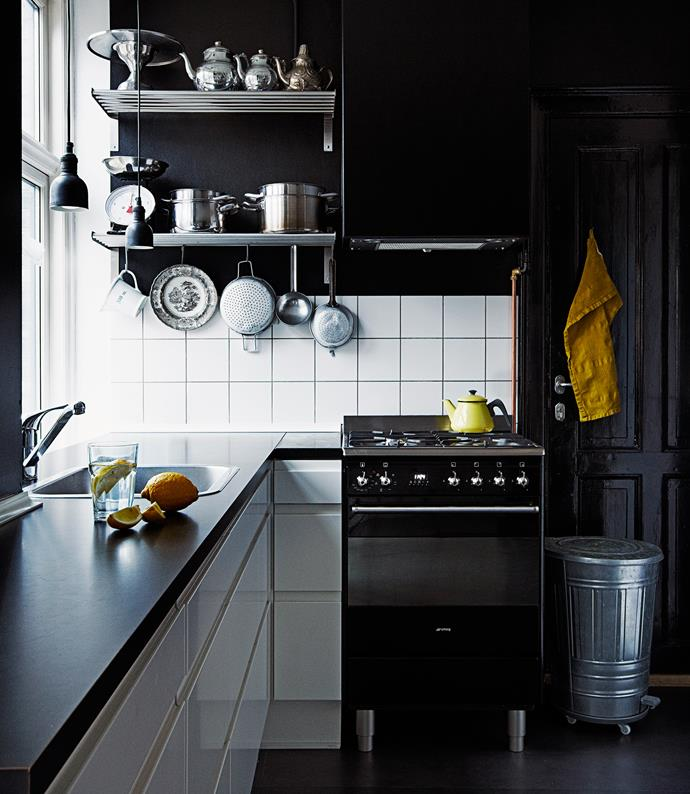 The black wall feature in the dining zone is repeated in the contemporary kitchen, tying the two areas together.