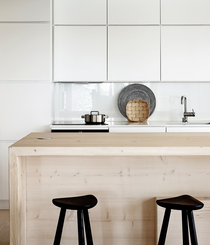 The open-plan kitchen is pared-down and simple, with smooth, handleless cabinets. The same timber that was used for the floors was used for the large kitchen island for a simple, unifying look.