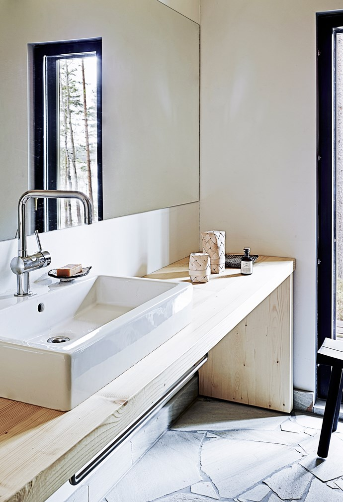 A large bathroom mirror, fixed to the wall, doubles the space and reflects the window view.