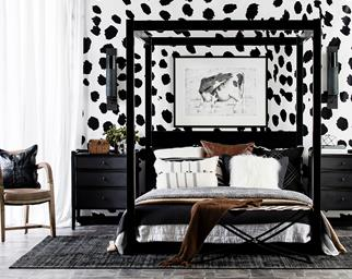 Four poster bed with black and white accessories and wallpaper