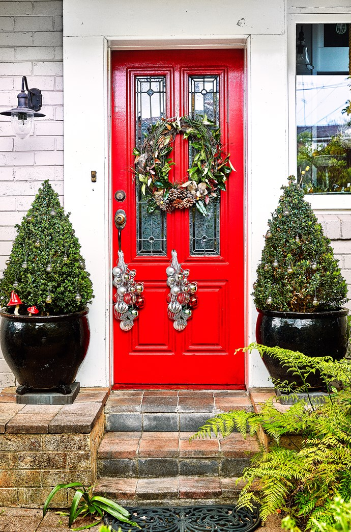 Two potted Christmas trees and a wreath, made by Steph's florist friend, create a warm welcome.