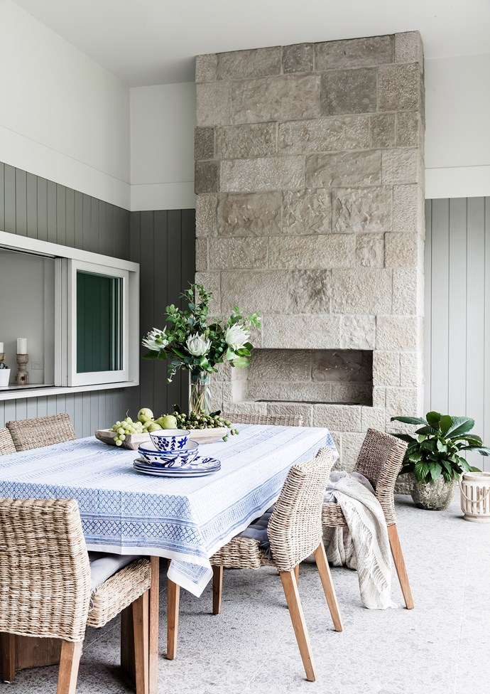 Stacking windows are used in place of a splashback in the kitchen to create a servery to the outdoor dining area. Dinnerware, [Few and Far](http://www.fewandfar.com.au/). Tablecloth and throw, [L&M Home](http://www.linenmoore.com.au/). Jo and Cameron have owned the dining setting for many years. Clancy Random Ashlar veneer (on chimneybreast) and Torino granite pavers, Outdoor](https://www.ecooutdoor.com.au/).