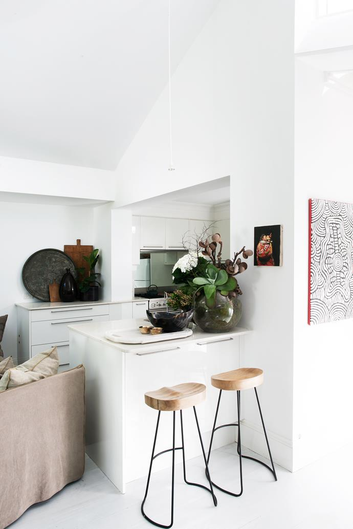 Artworks mingle with treasured mementos: coral, strings of beads, vibrant green glass bottles and vases.