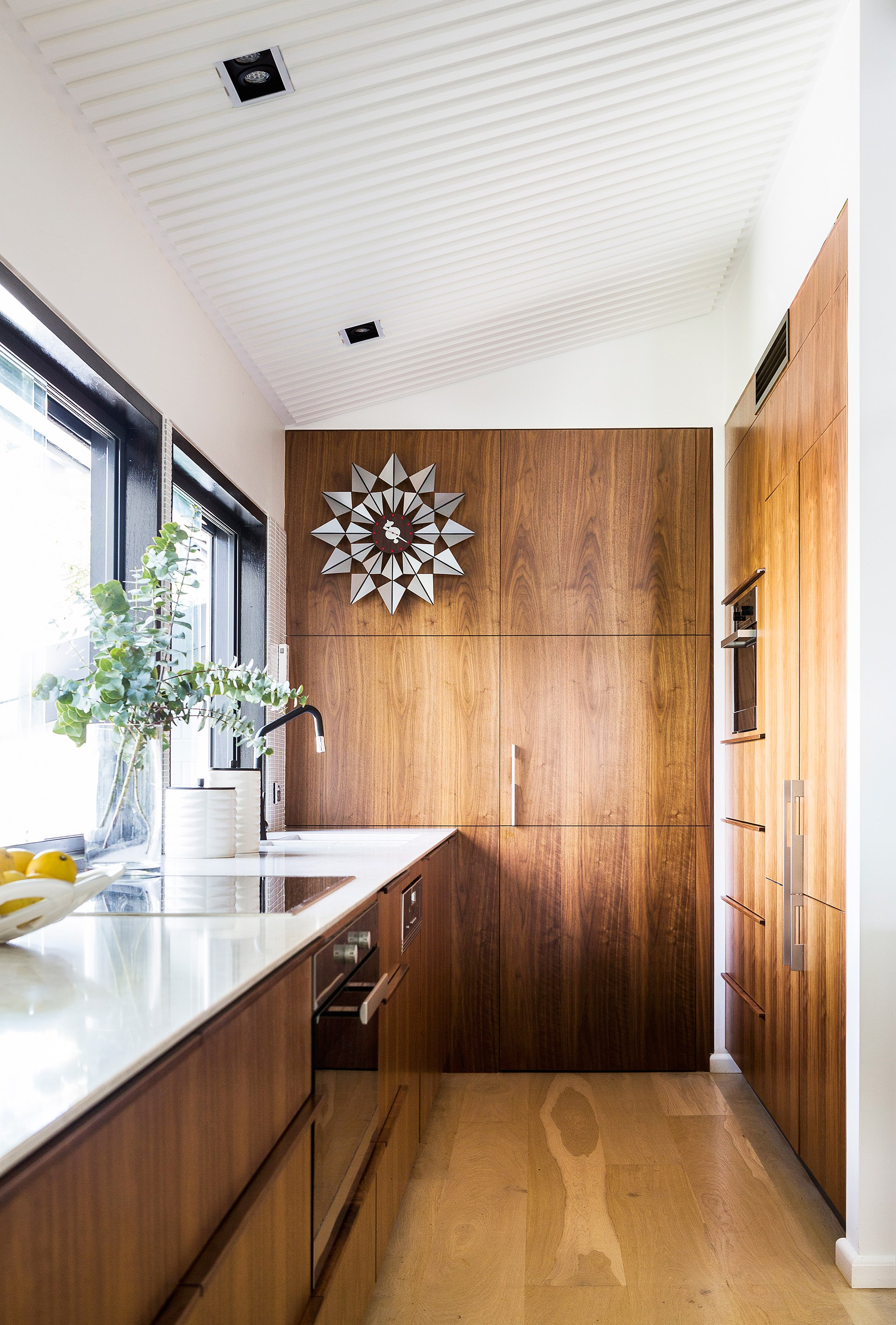 "The kitchen within this [revamped Modernist home](http://www.homestolove.com.au/modernist-home-gets-its-groove-back-4597|target=""_blank"") retains a retro flavour with American walnut joinery and a vintage George Nelson Butterfly clock. *Photograph*: Maree Homer"