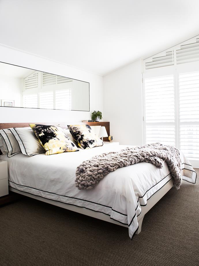 A large mirror above the bed reflects light entering the room, making it feel larger and brighter.
