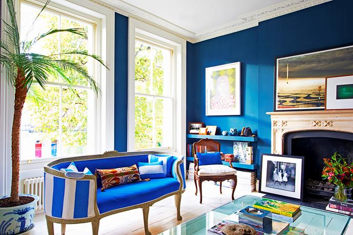In the living room, a large tropical palm tree – suggesting relaxed beachy holidays – provides a beautiful contrast to the more formal dark blue walls.