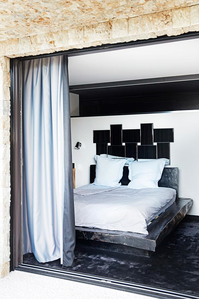 Double silk curtains in the master bedroom look luxurious and block out the morning light. The thick grey carpet enhances the luxe feel. The chunky timber bed was made in Bali.