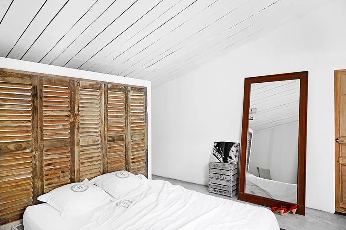 In the master bedroom, old shutters are transformed into a headboard on the bed side of the room and on the other side, they become part of a walk-in wardrobe, with open shelves attached to them for clothes. A stack of old fruit boxes by the mirror are used as a shelf.